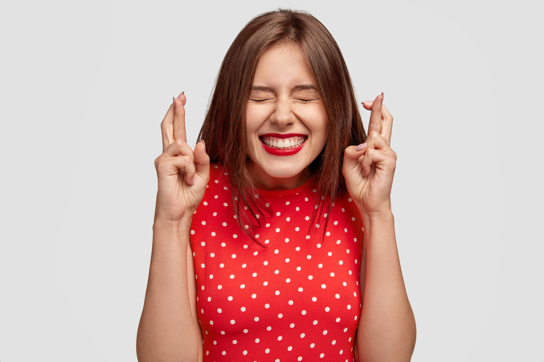 Mulher cruzando os dedos e de olhos fechados LCL Eventos